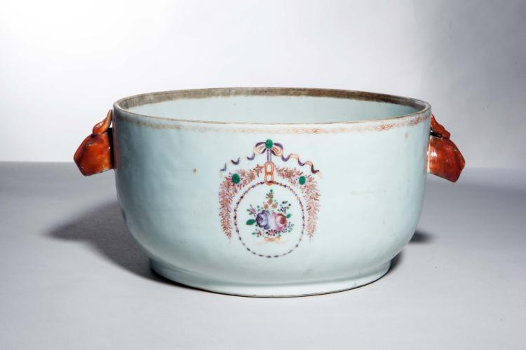 Terrine en porcelaine famille rose sertie de deux anses zoomorphes et orné en émaux polychromes d'un bouquet fleuri suspendu en blason dans une guirlande.