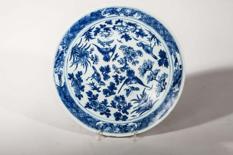 Plat en porcelaine blanc bleu illustré d'une assemblée d'oiseaux dans des bouquets fleuris.