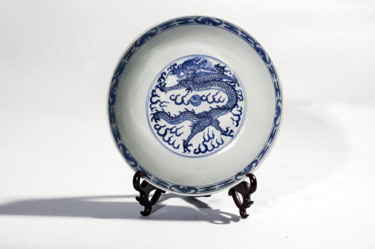 Coupe creuse en porcelaine blanche décorée en bleu cobalt sous couverte de dragons et nuages tsi.