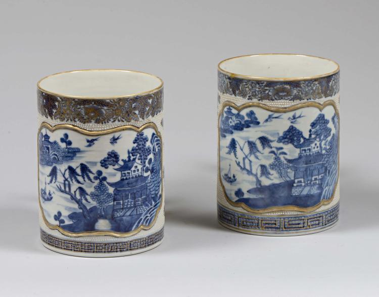 Paire de chopes de la Compagnie des Indes en porcelaine décorée en bleu cobalt sous couverte et rehauts d'or dans un cartouche polylobé d'un paysage en camaïeu bleu sur fond granité.