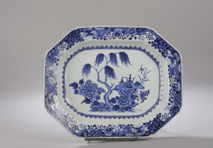Plat octogonal en porcelaine de la Compagnie des Indes décoré en bleu cobalt sous couverte d'objets précieux dans un bosquet fleuri.