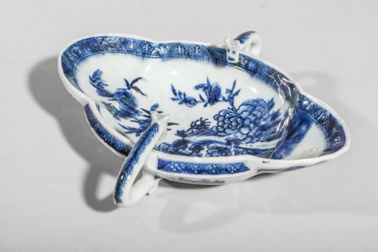 Saucière polylobée à double anse de préhension sertie de petites têtes en porcelaine blanche décorée en bleu sous couverte d'un bouquet de pivoines épanouies.