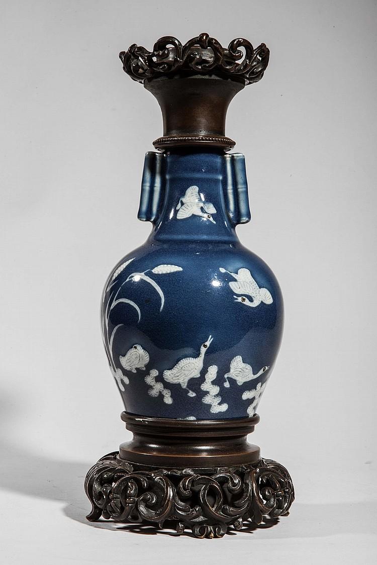 Vase balustre serti de deux anneaux cylindriques au col en porcelaine décoré de motifs floraux blanc sur fond bleu.