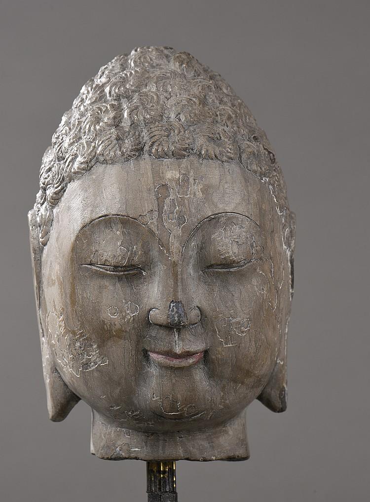 Tête de Buddha à l'expression de béatitude et de sérénité coiffée de  bouclettes organisée en rosaces tressées.