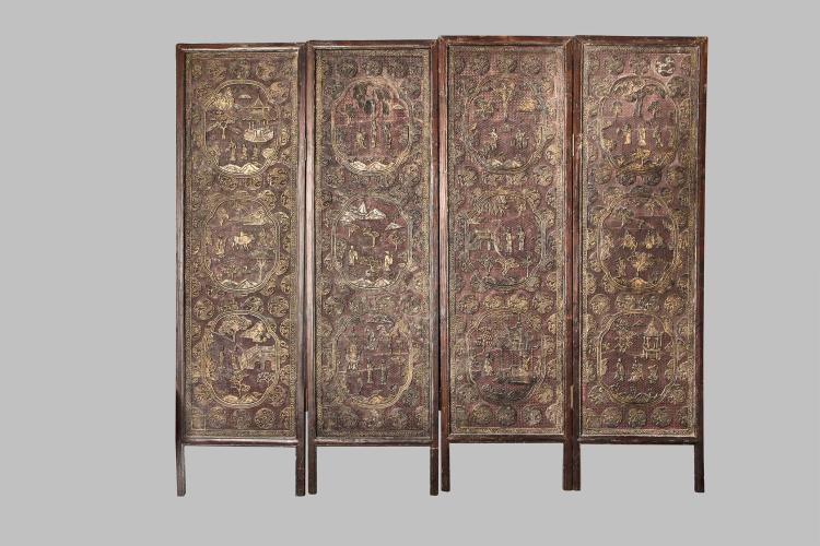Paravent à quatre feuilles ciselé de médaillons polylobés illustré de scènes traditionnelles sur fond de treillis laqués rouges dans un encart quadrangulaire une marque apocryphe.