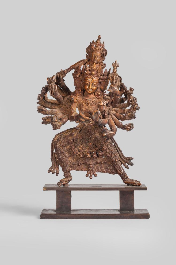 Durga debout en pratialidasana sous une forme à 16 bras et 4 têtes tenant les attributs tantriques et vêtu du tablier d'exorciste.
