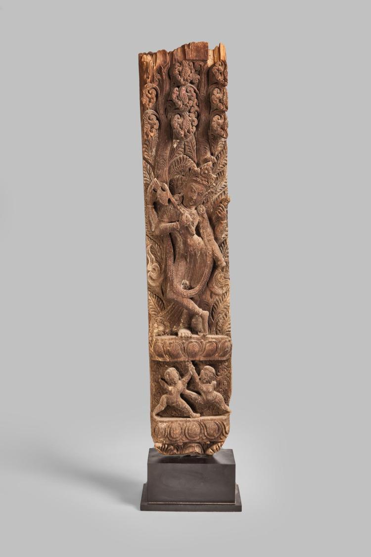 Poutre de soutènement de pagode illustrée d'un Krishna couronné sous une forme à quatre bras tenant  des attributs sur une base lotiforme supportée par un couple apsara gandharva et abrité par un arbre luxuriant.