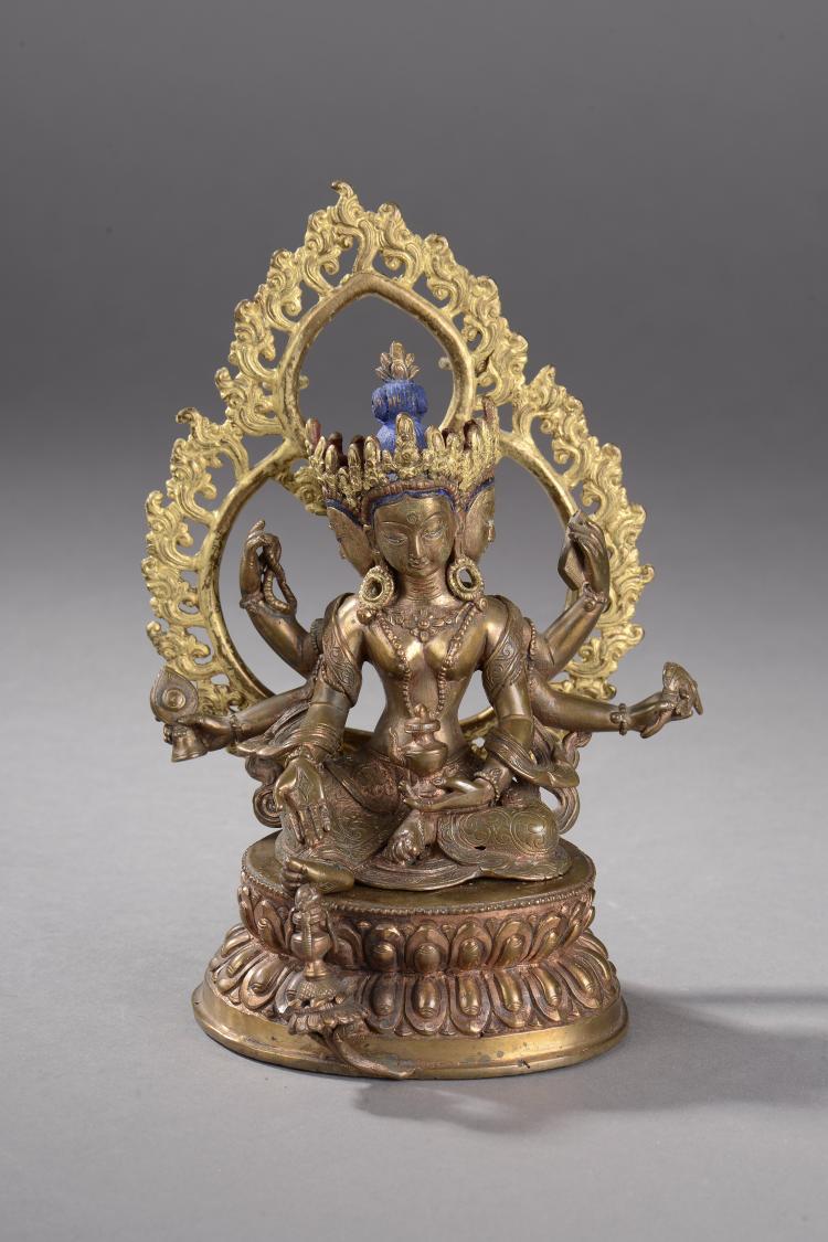 Prajanaparamita sous une forme à six bras et trois têtes assise en lalitasana  sur un socle lotiforme son pied reposant sur un kalasha auréolé d'une mandorle flammée.