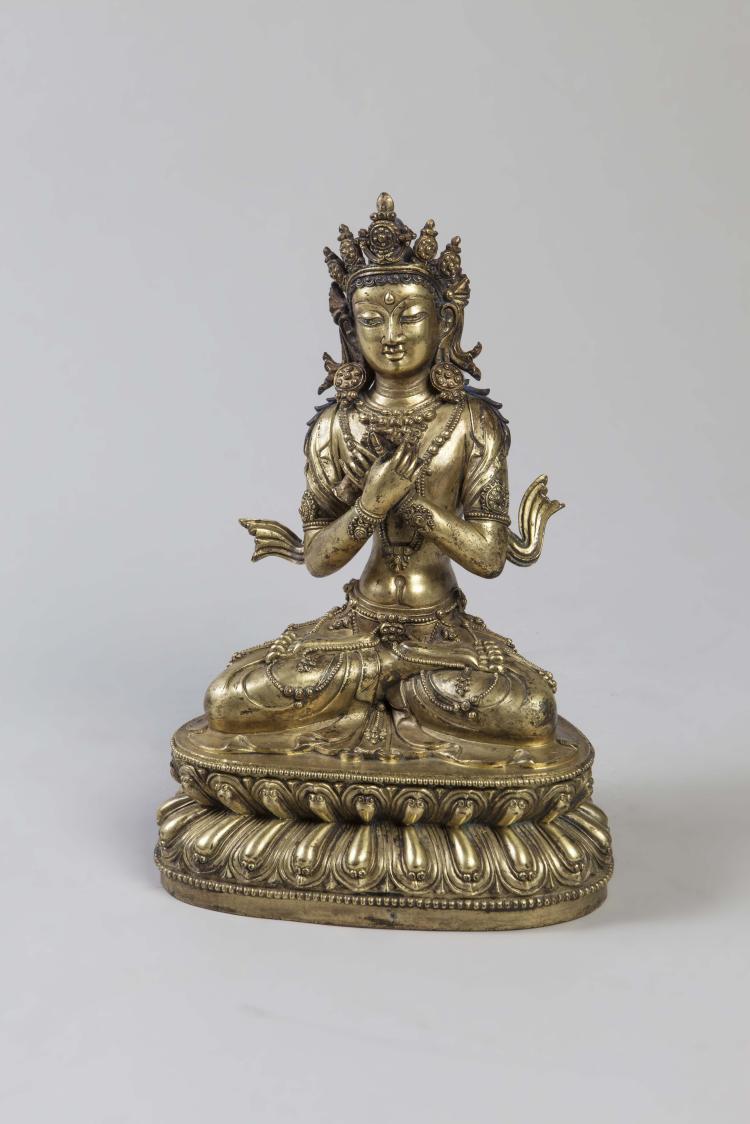 Vajradara assis en virasana sur un socle lotiforme à double rangées de pétales richement paré et couronné tenant de ses deux mains croisées sur la poitrine le vajra symbole masculin et la clochette ghanta symbole féminin.