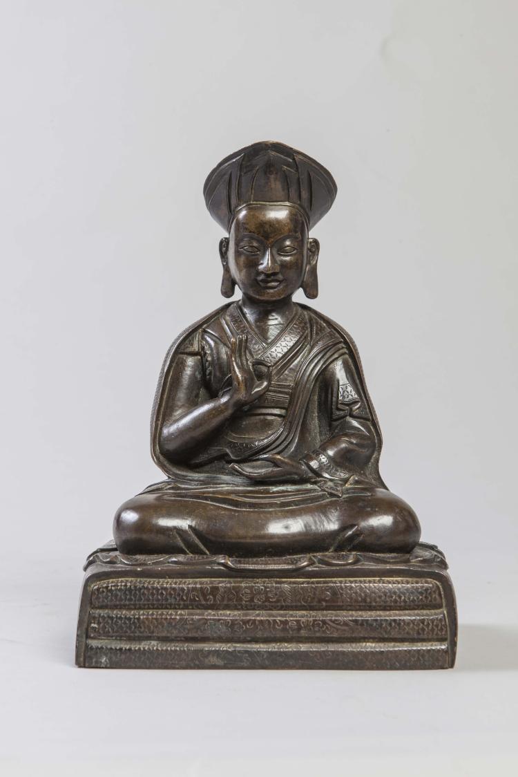 Portrait de lama coiffé du bonnet ecclésiastique vêtu d'une robe monastique assis en méditation sur un socle de coussins,