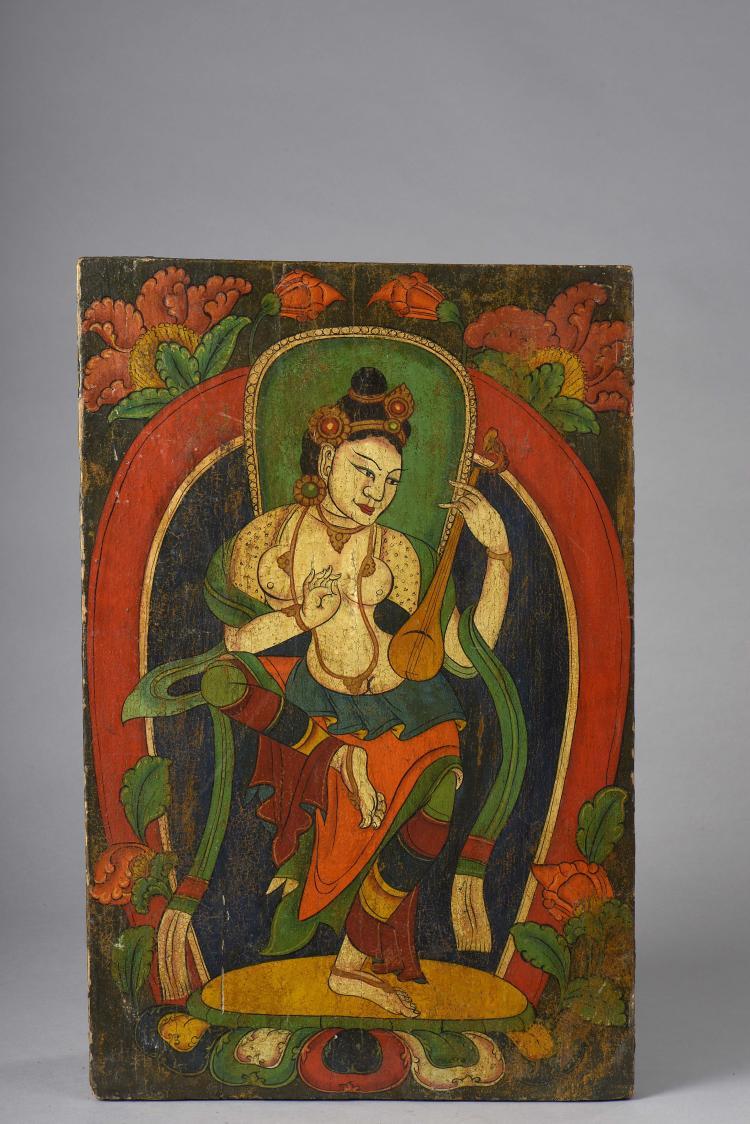 Panneau d'architecture intérieur de monastère illustrant une Apsara dansante sur un autel lotiforme tenant un instrument à corne vêtu d'un dhoti et d'écharpes bouillonnanates coiffé d'un diadème à pétale et paré de joyaux dans un décor floral.