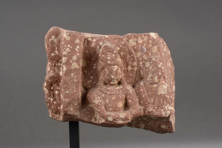 Haut relief de pilier ciselé d'un buste de divinité.