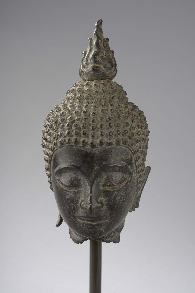 Tête de Buddha coiffée de fines bouclettes surmontée de la protubérance crânienne ushnisha d'où s'échappe un rasmi flammé symbole du départ de l'âme.