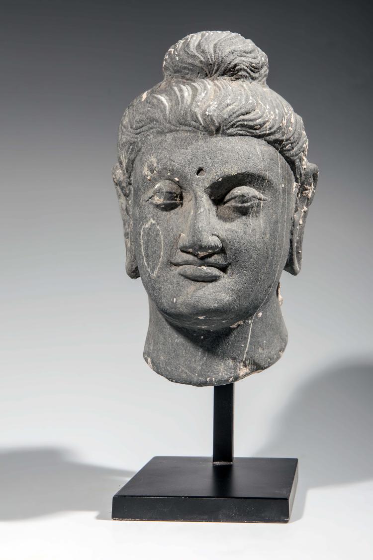 Tête du Boddhisattva Maïtreya au visage à 'expression sereine la coiffure bouclée en larges ondulations retenues en un chignon symbolisant la protubérance crânienne ushnisha.