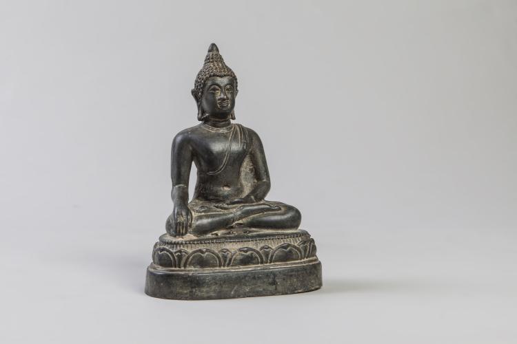 Buddha Maravijaya assis en virasana sur un socle lotiforme vêtu de la robe monastique lui couvrant l'épaule gauche.