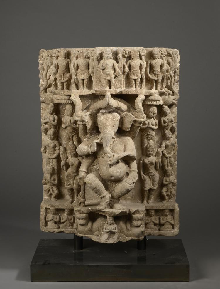 Stèle illustrant Ganesh dansant entourée au registre supérieure de divinités du panthéon hindou et au registre inférieur d'adorants et de deux lions d'échiffre et accompagnée de part et d'autre d' Apsaras en tribanga.