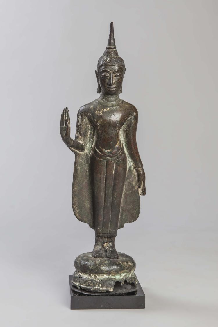 Buddha debout sur un tertre circulaire vêtu d'une robe monastique aux pans déployés,