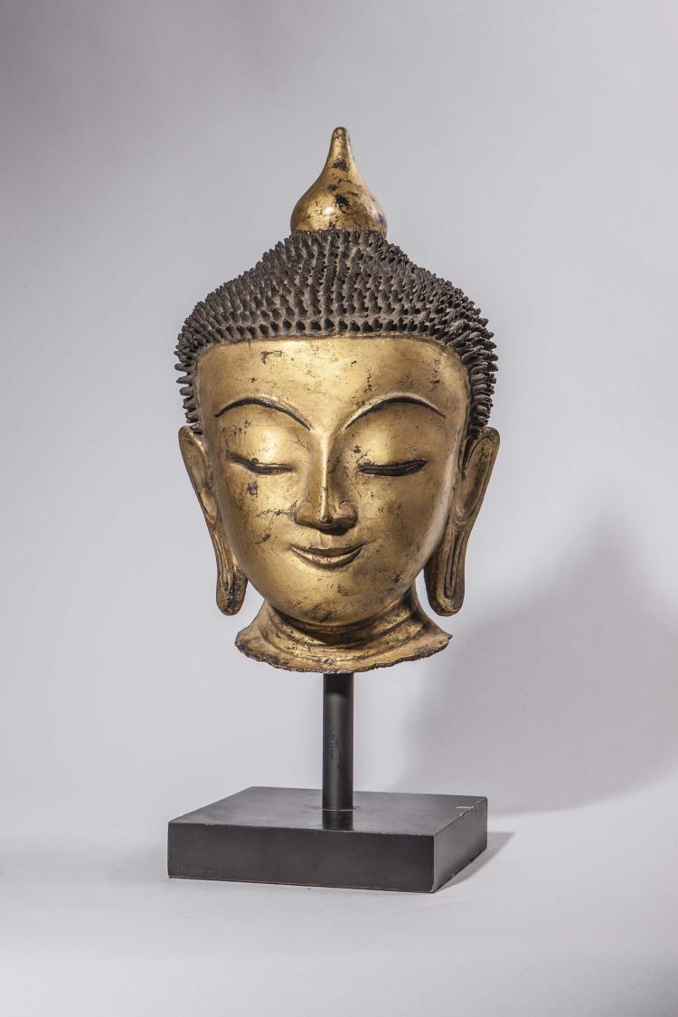 Tête de Buddha à l'expression sereine coiffé de fines bouclettes surmontée d'un rasmi.