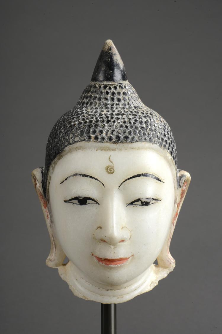 Tête de Buddha marqué de l'urna au milieu du front à la coiffure bouclée sommée d'un rasmi piriforme.