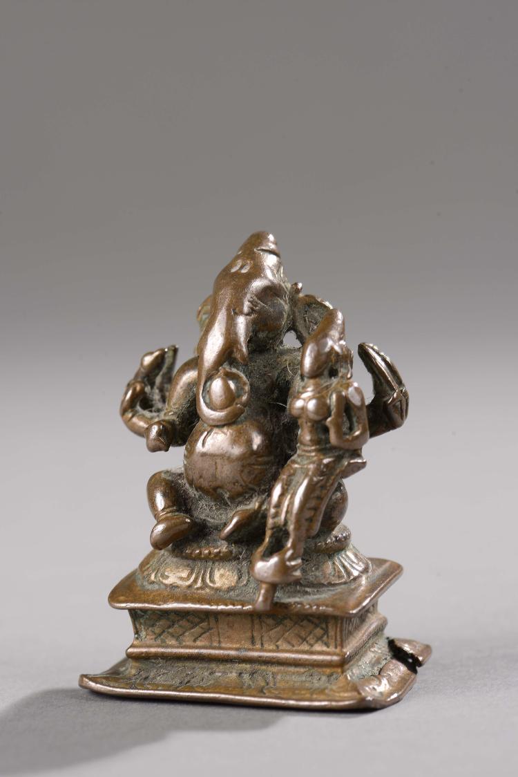 Ganesh assis sur un socle quadrangulaire sous une forme à huit bras sa shakti sur son genoux gauche.
