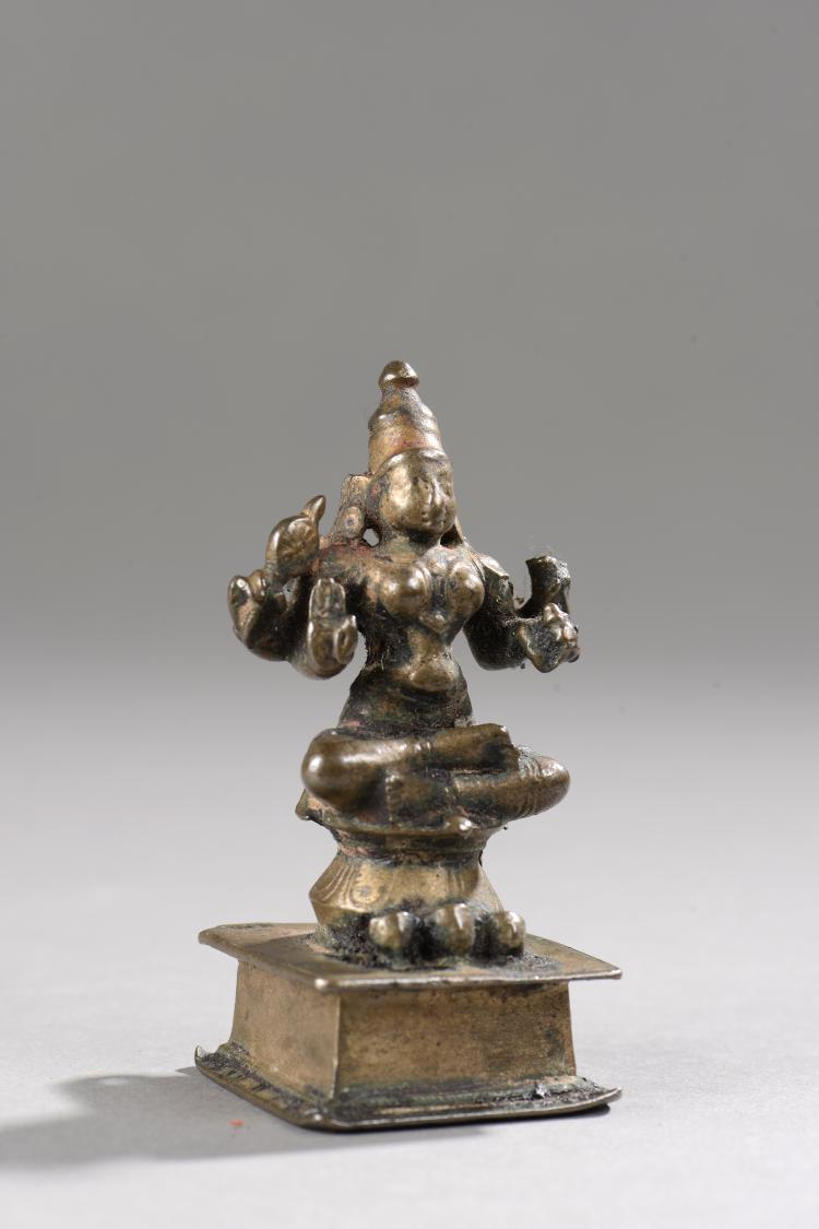 Lakshmi assise en dhyanasa sur un haut tertre sous une forme à quatre bras tenant le çakra et divers attributs coiffée d'une haute tiare mukuta.