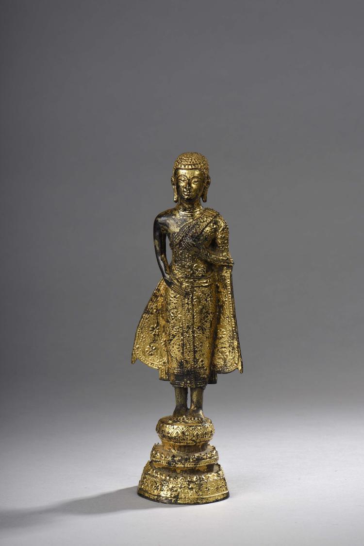 Adorant disciple du Buddha debout sur un haut tertre vêtu d'une robe monastique ouvragée aux pans déployés.