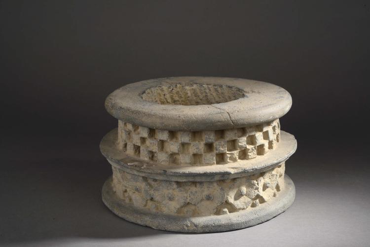 Base de stupa ciselée sur deux niveaux d'une frise florale et d'une frise géométrique à damier.