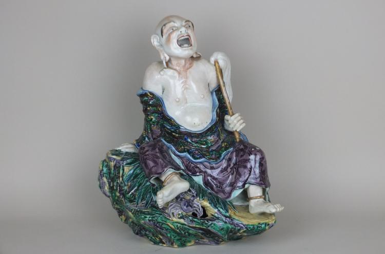Lohan en porcelaine polychrome figuré la tête relevée,