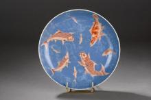 Large assiette en porcelaine de la famille rose illustree d' une assemblee de poissons en emaux corail sur fond de transparence d' eau bleue.