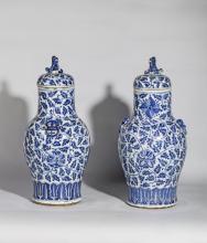 Paire de vases couverts moules d' anses a tetes de chimere a l' epaulement et surmonte de chien de Fo en tenon de prehension, couvercle en porcelaine blanche decoree en bleu cobalt sous couverte de rinceaux fleuris et frises de palmettes.