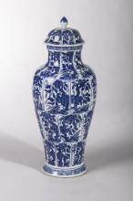Paire de vases balustres couverts en porcelaine blanche decores en bleu cobalt sous couverte d' arbustes dans des reserves polylobees et de frises geometriques.