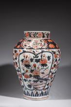 Vase en porcelaine imari a decor de branchages en reserve sur fond fleuri.