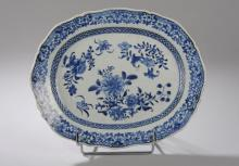 Plat ovale en porcelaine blanche decore en bleu cobalt sous couverte de motifs floraux.