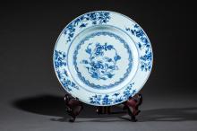 Suite de cinq assiettes de la Compagnie des Indes en porcelaine blanche decoree en bleu cobalt sous couverte de motifs floraux et paysages.