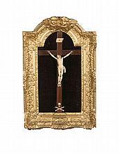 Christ en ivoire sculpté dans un cadre en bois doré à décor de têtes d'an