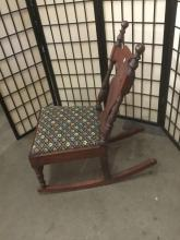 Lot 338: Antique carved wood rocking chair with a floral stitched seat