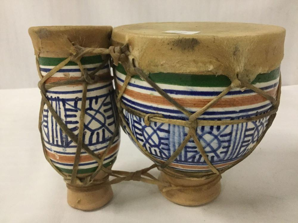 Lot 389: Pair of lashed Moroccan tom-tom drums having rawhide bindings and painted designs