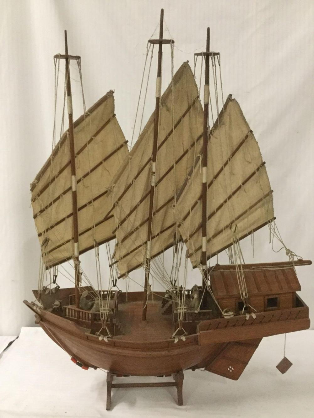 Lot 300: Large vintage wood sailing ship model with cloth sails, wood stand and ceramic Asian passenger