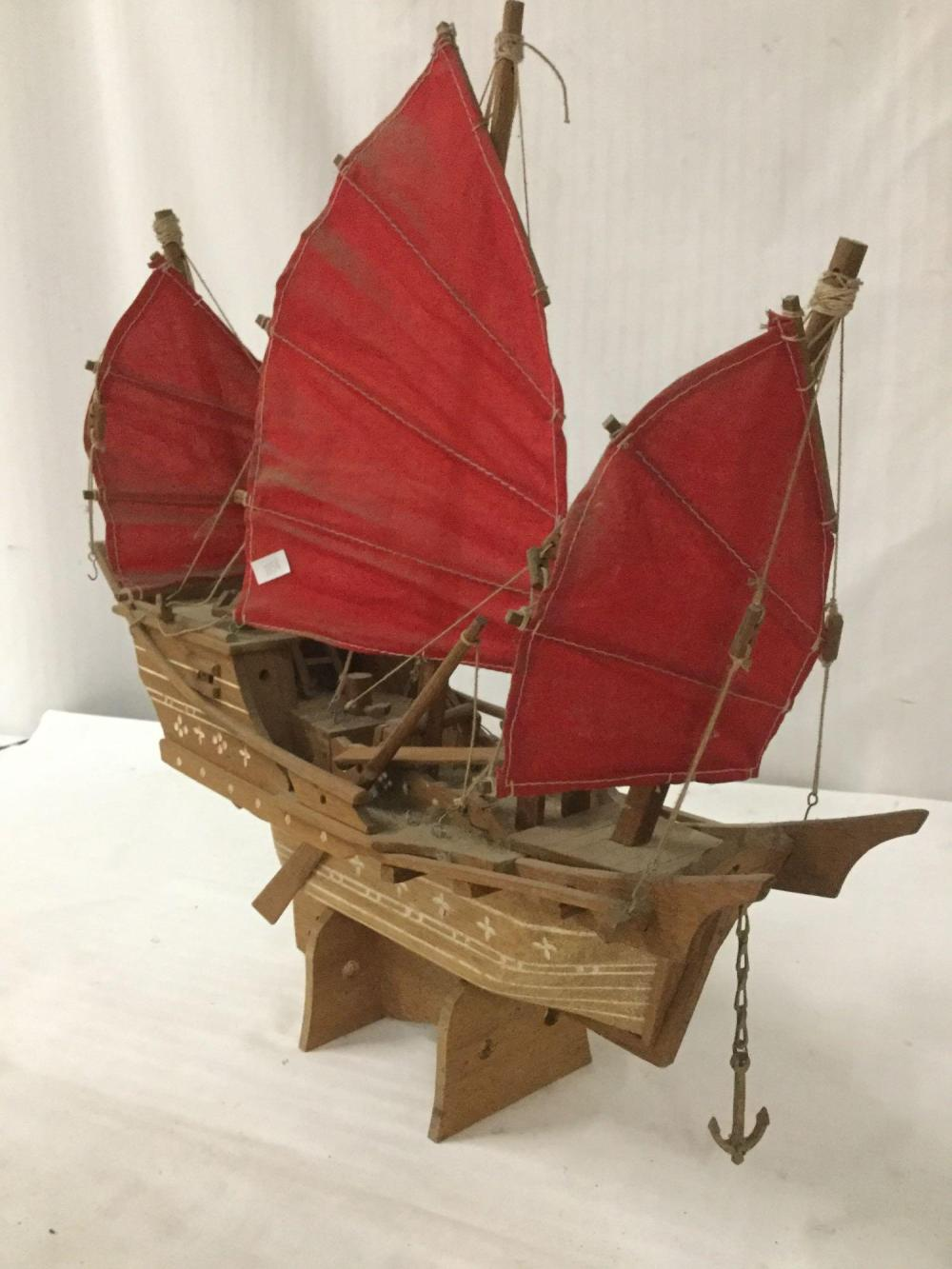 Lot 301: Vintage wooden ship model with wood stand and red cloth sails
