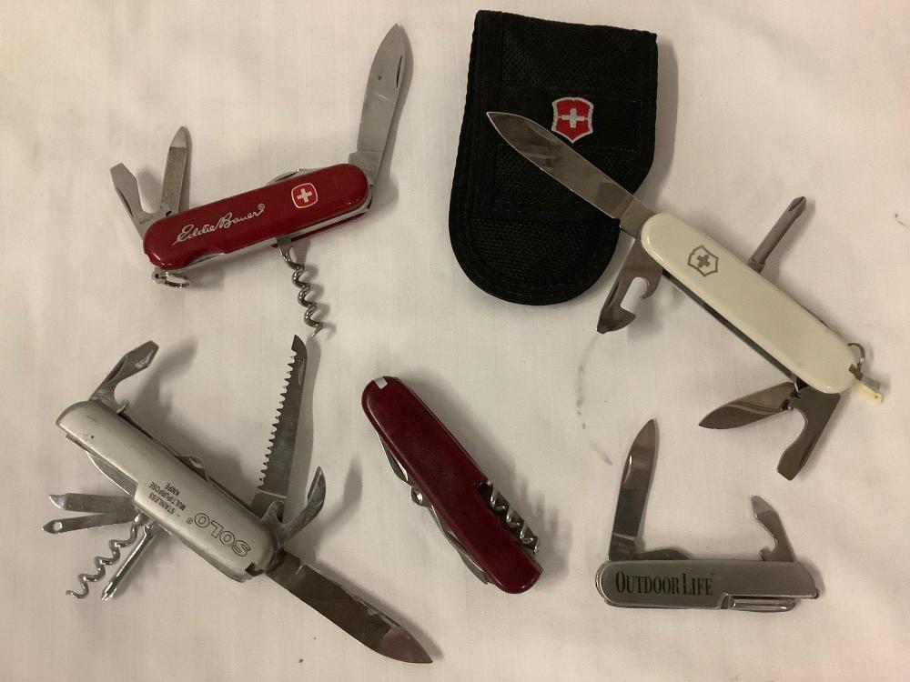 Lot 347: 4 pocket knives; Swiss Army white Victorinox w/ pouch, Eddie Bauer Swiss Army Knife, etc