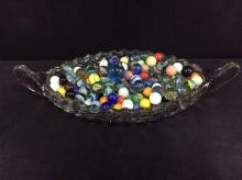 a crystal boat dish filled with vintage marbles