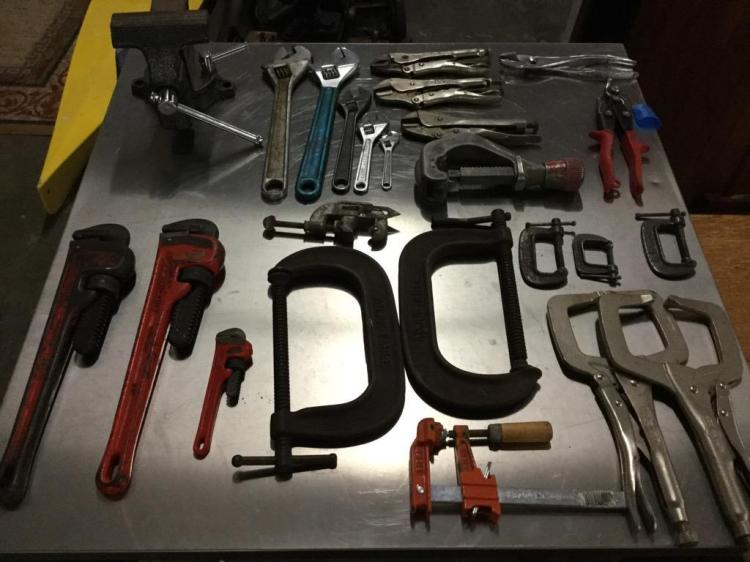 A large collection of vise grips, clamps, pipe wrenches, and a vise.