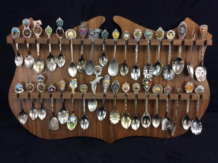 Huge collection of collectors spoons on large shield display