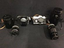 A Canon 35mm TL camera body in case, and 2 Canon lenses, a 85mm and a 200mm