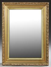 American Victorian Gilt and Gesso Mirror, c. 1900, with a relief c-scroll frame around wide cove molding and a rectangular plate, H....