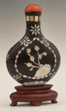 Chinese Black Lacquer Mother-of-Pearl Inlaid Snuff Bottle, early 20th c., with floral inlay and a red stone stopper, on a carved har...