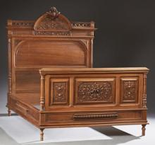 French Henri II Carved Walnut Double Bed, late 19th c., the arched headboard with a scrolled leaf crest over relief leaf carving abo...