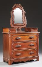 American Victorian Carved Walnut Dresser, c. 1880, the shaped mirror with a pierced crest and a wide frame, within a serpentine yoke...
