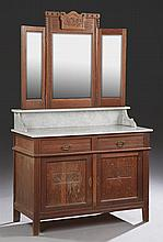 Continental Carved Oak Marble Top Washstand, early 20th c., the arched carved back over a trifold wide beveled mirror, above a figur...