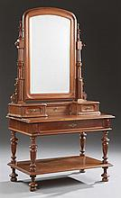 French Carved Walnut Vanity, late 19th c., the arched top wide beveled swivel mirror over three drawers, on a base with a long friez...